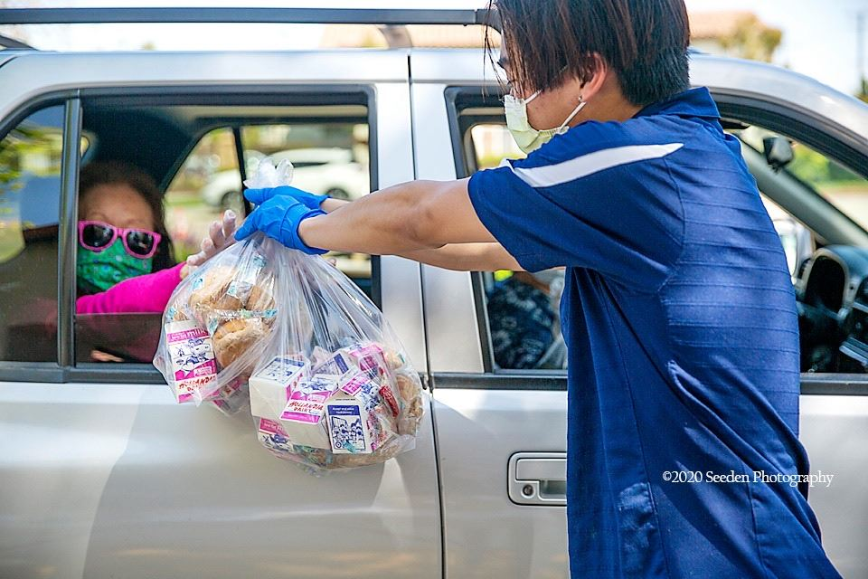 Masked Senior in car accepting Meals on Wheels from a staff member